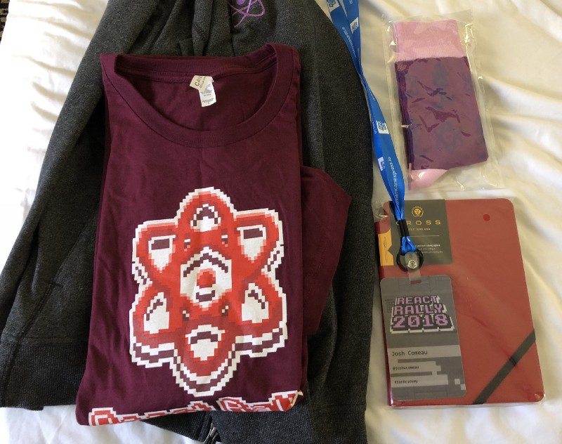 A set of swag including a T-shirt, a hoodie, socks, and a personalized notebook