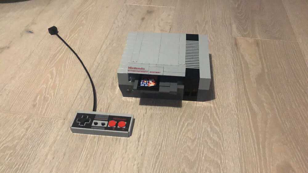 A life-size Nintendo Entertainment System console, made out of lego, with a controller (also made out of lego)